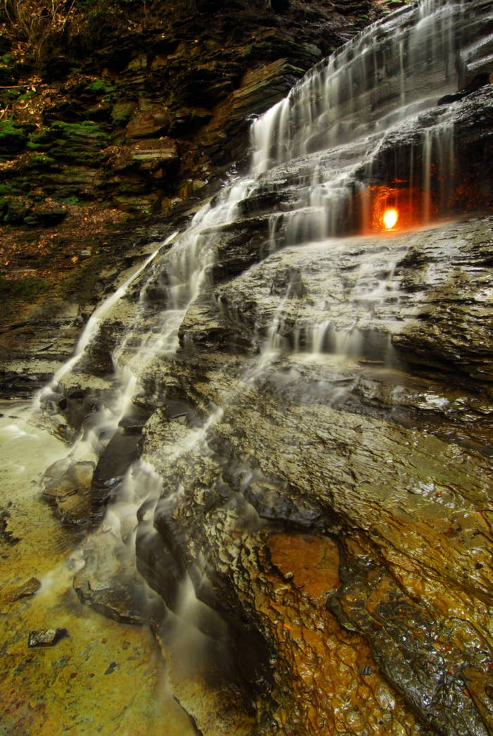 """Trail name: Eternal Flame Falls TrailLocation: Chestnut Ridge Park in Orchard Park OK, so it's not really an """"eternal"""" flame, but it's a pretty cool natural phenomenon. There is a small fissure right below the waterfall that naturally emits methane gas. If there's no light when you visit, it's pretty easy to start up with a barbecue lighter. 🔥"""