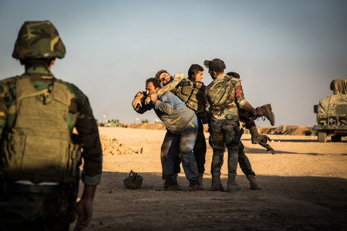 A Kurdish soldier is carried by his comrades after being badly wounded by mortar fire during a mission north of Mosul. Doctors later amputated one of his legs.