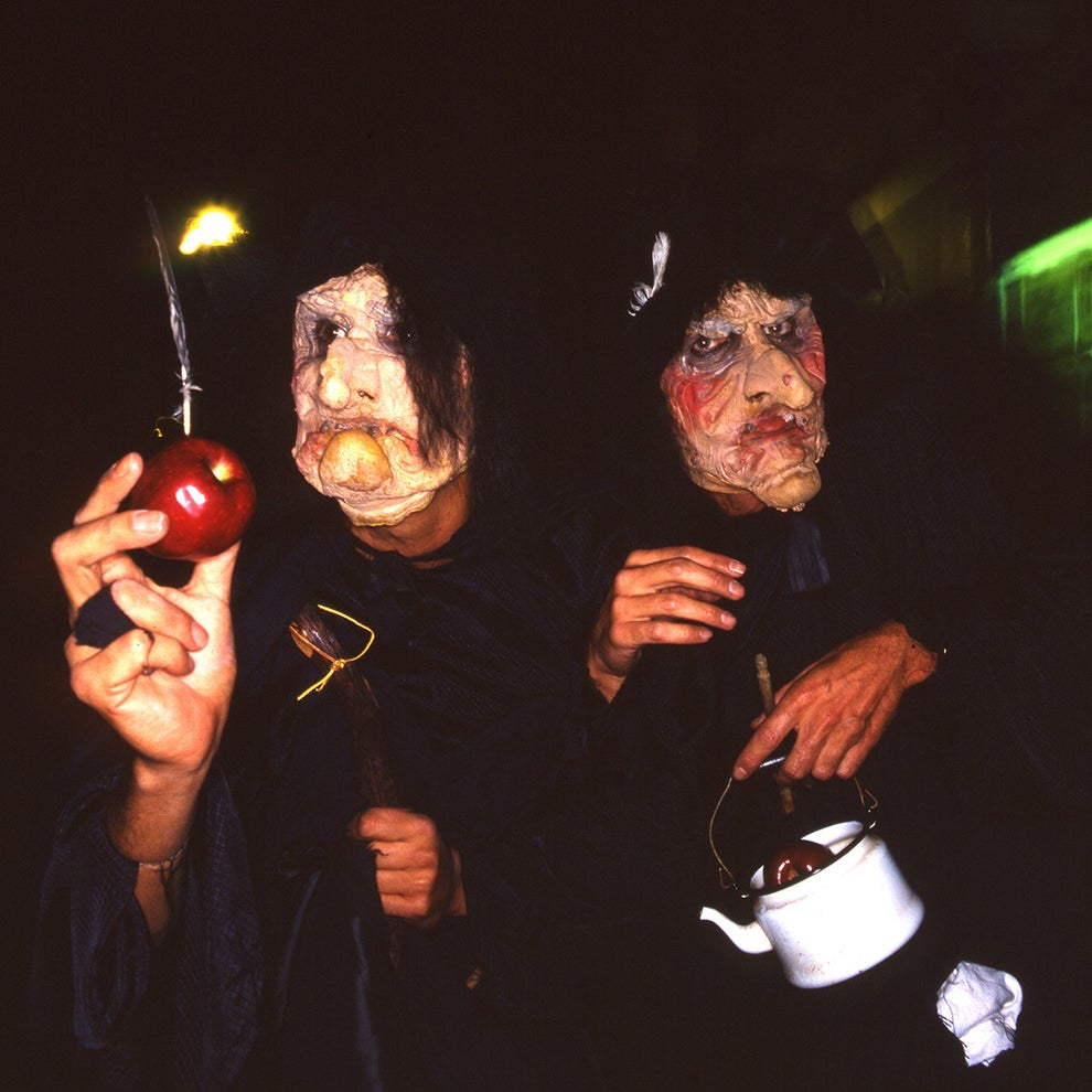 A pair of wicked witches offering a delicious apple for the taking...