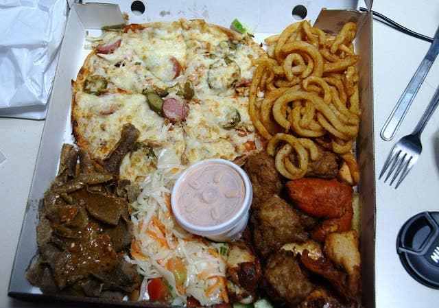 ポテト、ピザ、フライドチキンなどが盛りだくさん入ったボックスは、ファーストフード店で販売される。