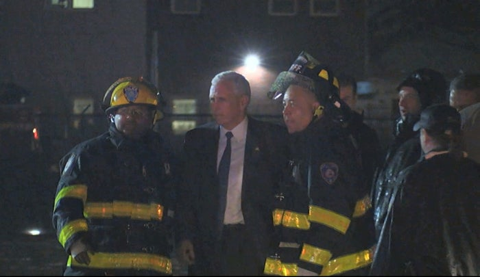 Mike Pence talks with firefighters after his campaign plane slide off the runway Thursday.