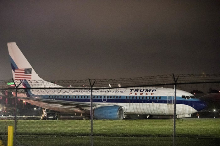 Pence's campaign airplane sits partially on the tarmac and the grass after sliding off the runway in New York.