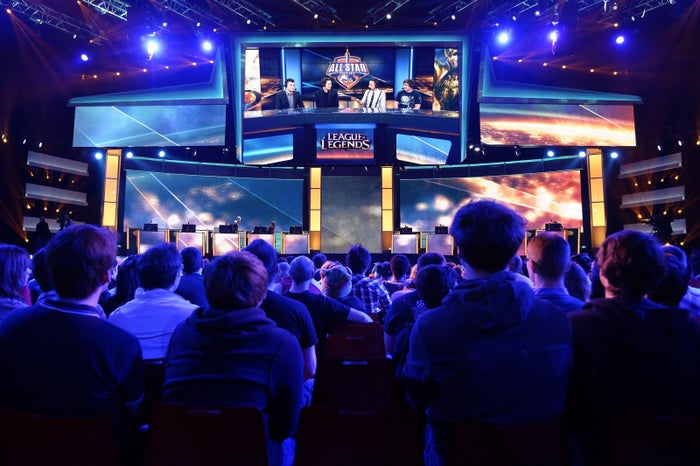 Visitors listen to commentators after a battle between international teams during a League of Legends tournament on May 8, 2014 in Paris.