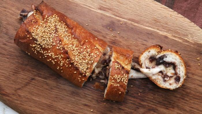 あんことチーズのスタッフドバゲット2〜3人分材料:バゲット 1本モッツァレラチーズ(2cm角切り) 100g粒あん(こしあんでも可) 100g溶かしバター 30g白ごま 適量作り方1. ボウルに粒あんとモッツァレラチーズを入れて混ぜ合わせる。2. バゲットの両端を切り落として中身をくりぬき、(1)を詰めて、クッキングシートを敷いた天板にのせる。3. 溶かしバターをかけて白ごまをふり、230℃に予熱したオーブンで10分焼いたら、完成!