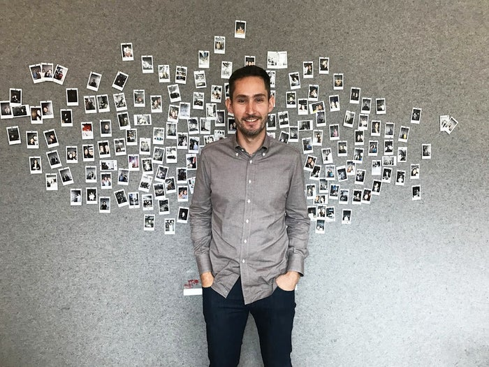 Instagram CEO Kevin Systrom in front of a photo wall at the Blue Bottle café inside the company's new headquarters building.
