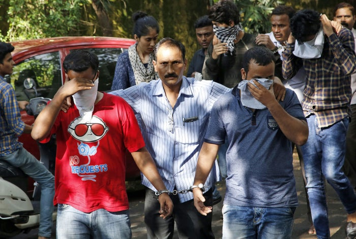 A police official, center, escorts two men outside the court in Thane, India.