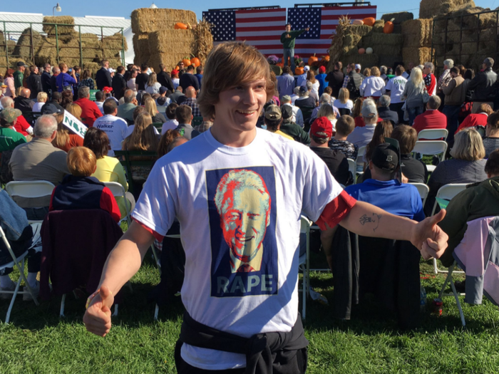 A Trump supporter shows off his t-shirt while Scott Walker speaks on the stage behind him.