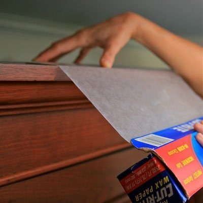 Dust the tops of all of your kitchen cabinets and any other furniture that almost reaches the ceiling, then lay down a layer of wax paper to prevent future dust.