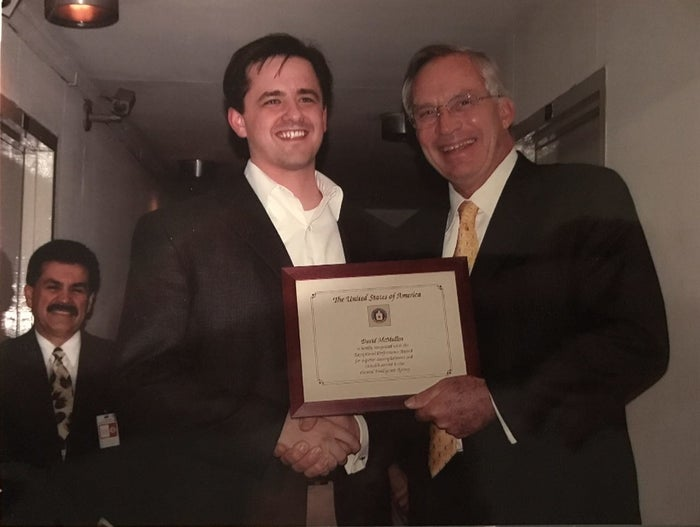 McMullin accepts a certificate from CIA Director Porter Goss. Jose Rodriguez, the former director of the CIA's National Clandestine Service, is in the background.