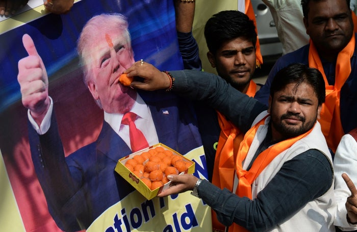 Activists of India's Hindu Sena offer sweets to a poster of President-elect Donald Trump.