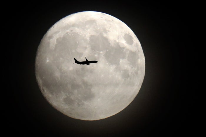 A jet flies in front of the moon on its approach to Heathrow airport in London.