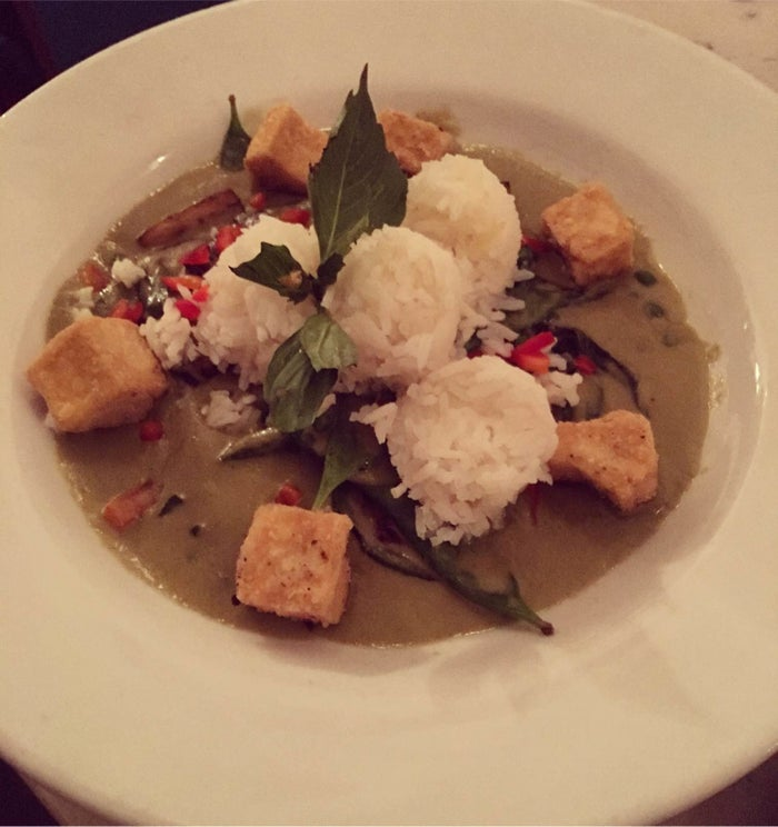 """The rich and creamy Green Curry is made with coconut milk infused with lemongrass, galangal, makrut lime leaves, and Thai basil with green peas, sweet peppers, fresh garlic, Japanese eggplant, and crispy fried tofu. It is served with four """"scoops"""" of jasmine rice. For those with high heat tolerance, you can order the dish """"spicy as hell."""""""