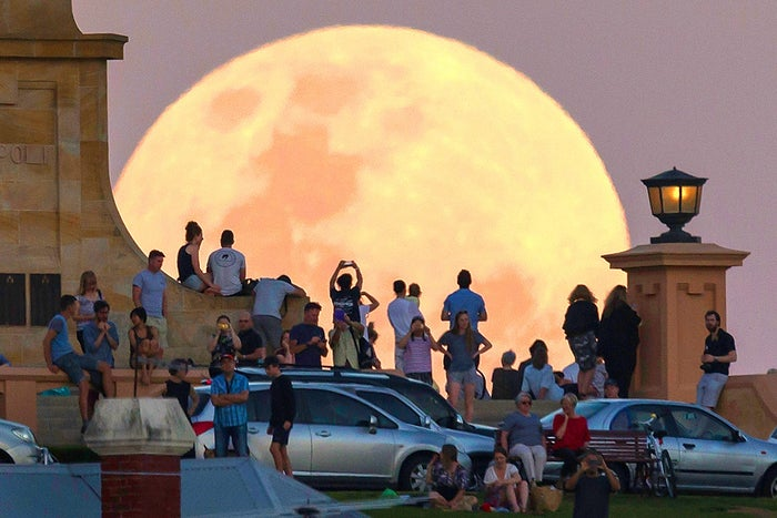 Crowds look on as the super moon rises behind the Fremantle War Memorial at Monument Hill in Fremantle, Australia.