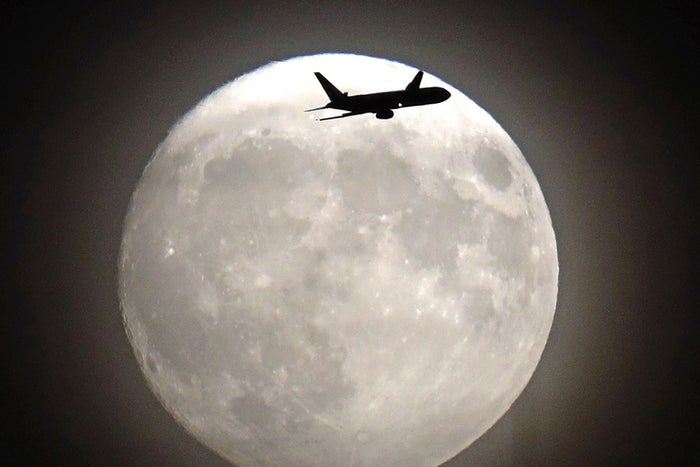 A commercial jet flies in front of the moon on its approach to Heathrow airport in west London.