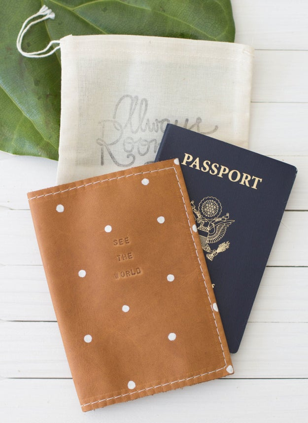 A dotted leather passport cover etched with a subtle piece of advice.