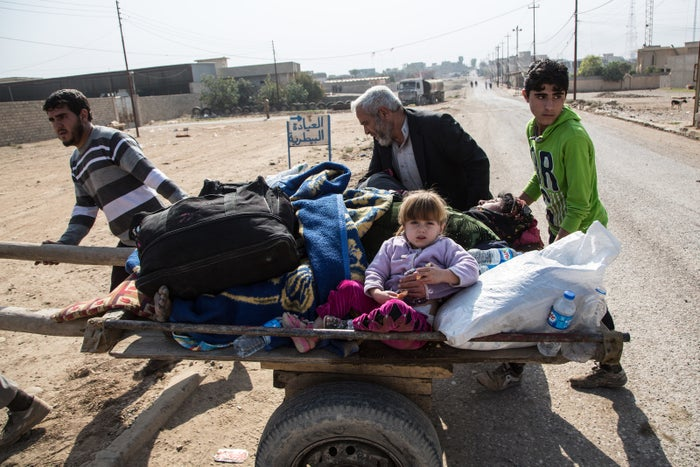 A woman's family pushes her on a cart after she was wounded by an ISIS mortar bomb.