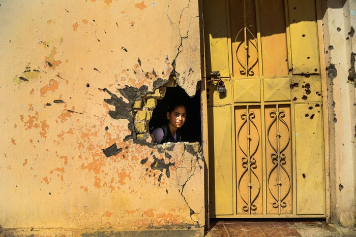 A young girl looks through a hole in the wall of a school in Ramadi.