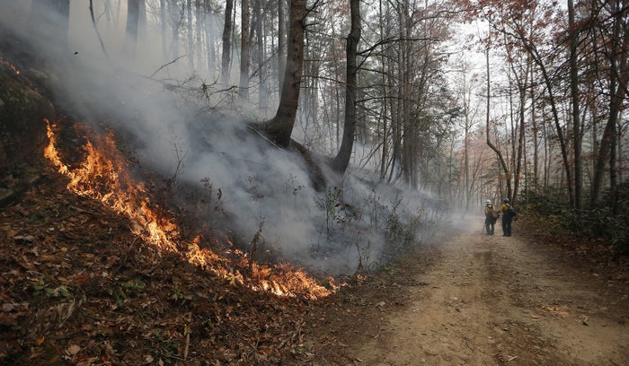 Firefighters walk down a dirt road a wildfire burns a hillside Tuesday in Clayton, Georgia.