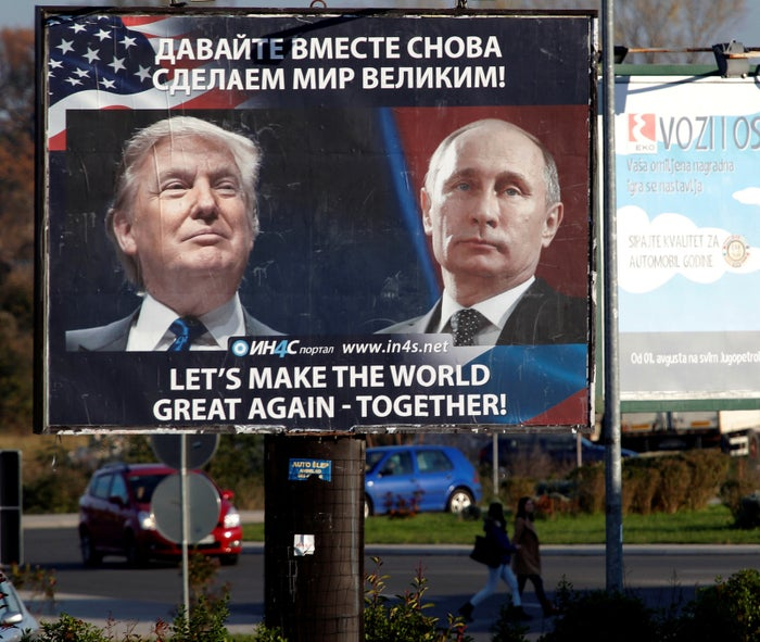Pedestrians cross the street behind a billboard showing a pictures of US president-elect Donald Trump and Russian president Vladimir Putin in Montenegro.