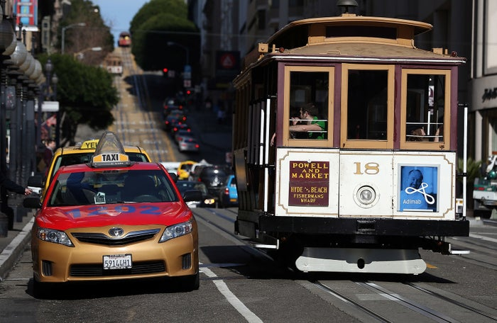 A cable car passes a line of taxicabs as they wait for fares in front of the St. Francis Hotel on Jan. 21, 2014, in San Francisco.