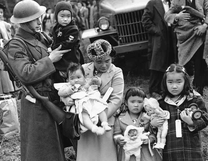 1942年、3月30日。ワシントン州ベインブリッジアイランドからやってききたキタモト・シゲホさんと彼女の子供たち。カルフォルニアに237人の日本人を向かわせるため指揮をとったジョージ・ブッシー伍長が、キタモトさんの末っ子を抱いている。