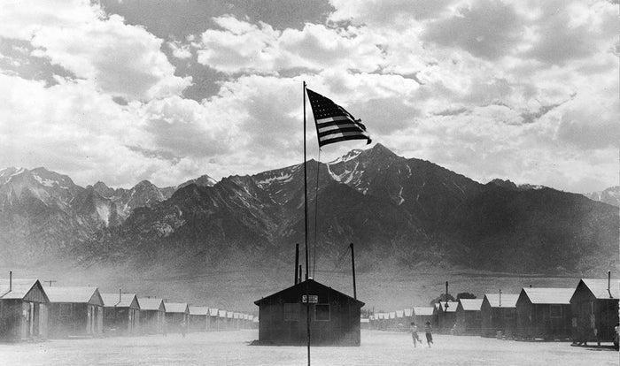 1942年7月、日系人強制収容所で風になびく星条旗。カリフォルニア州のマンザナー強制収容所は山に囲まれていた。