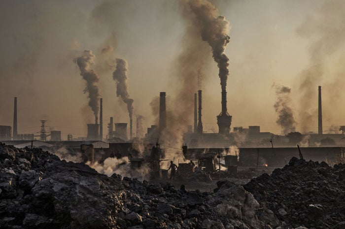 Smoke billows from a large steel plant as a laborer works at an unauthorized steel factory in Inner Mongolia.