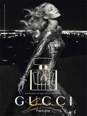 A elegant women posing for a Gucci perfume advertisement. She shows off womanly features including the long, waving hair, beautiful and fancy dress, and serene expression.