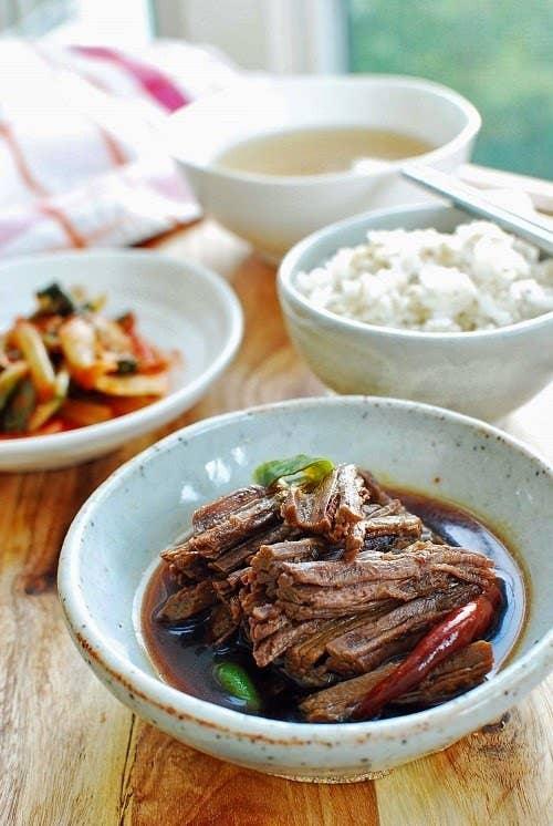 What is it? Soy-drenched beef strips.This is always the first banchan (side dish) to disappear. It's made by boiling beef in a seasoning of sugar, soy sauce, chili peppers, and vegetables until tender, and usually served with hardboiled eggs braised in soy sauce. Recipe here.
