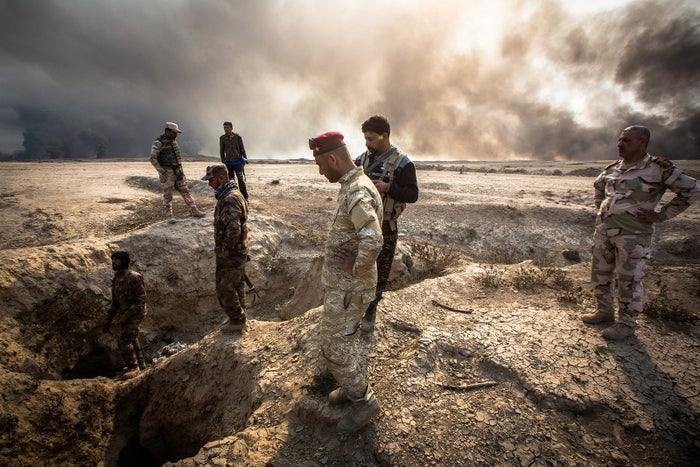 Soldiers examine the land near a site where the body of a man executed by ISIS was found.