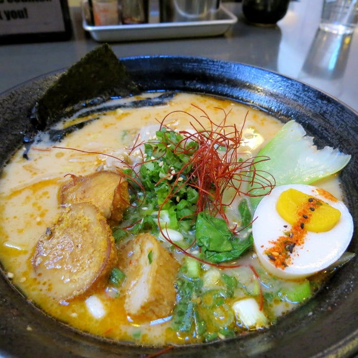 """Yes, that's a vegan egg sitting in the spicy ramen bowl at """"Top Chef"""" winner Ilan Hall's all-vegan ramen bar, Ramen Hood. Ramen Hood is situated in the bustling Grand Central Market food hall.The ramen (available both in OG or spicy style) is made with a creamy sunflower seed broth, and is filled with thick noodles and delicious veggies, including king oyster mushrooms. The vegan egg is a well worth it $2 add-on. It doesn't add a lot of flavor, but the experience, including biting into the juicy yolk, is terrific.This is must-try ramen.Ramen Hood is located Downtown in Grand Central Market at 317 S Broadway, Los Angeles, CA 90013."""