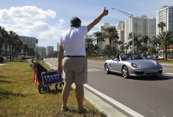 Donald Trump supporter Al Beaushaine waves to motorists outside a polling station in Clearwater, Florida.