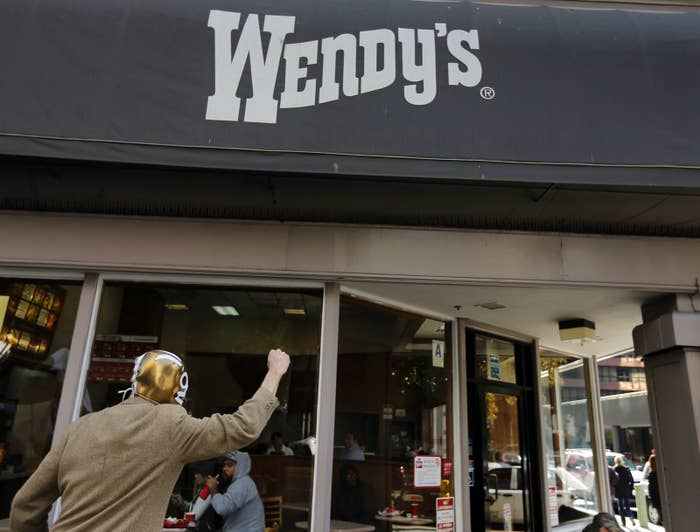 A protester shouts outside outside a Wendy's fast food outlet in support of a nationwide strike and protest at fast food restaurants to raise the minimum hourly wage to $15.