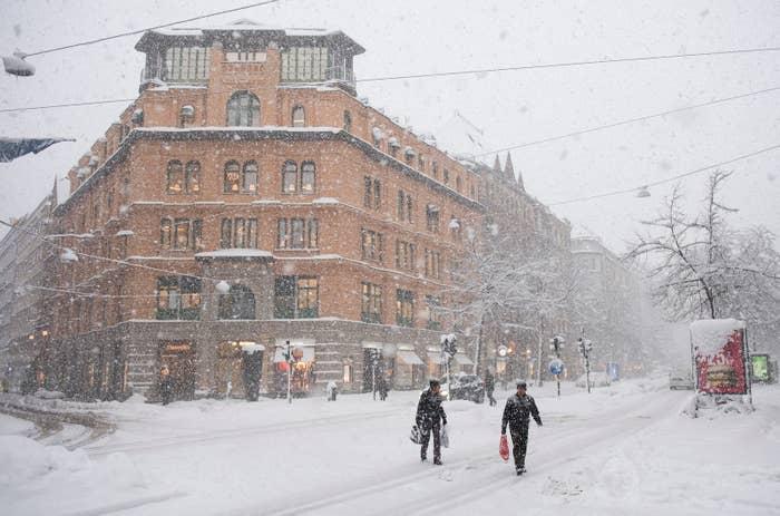 2016年11月9日、ストックホルム市内にて雪の嵐の中を歩く人々。