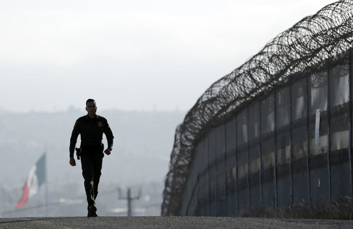 Border Patrol agent Eduardo Olmos walks near the secondary fence separating Tijuana, Mexico, background, and San Diego.