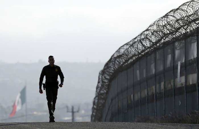 Border Patrol agent Eduardo Olmos walks near the secondary fence separating Tijuana, Mexico, background, and San Diego.
