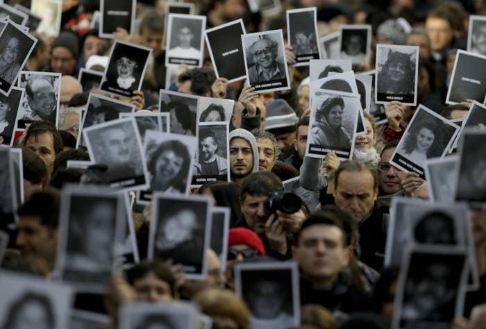 Cientos de personas sostienen fotos de las víctimas del atentado de la AMIA que dejó 85 muertos en 1994.
