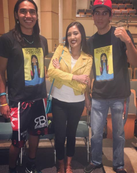 Erica Moore with two people wearing one of her Standing Rock T-shirt designs.
