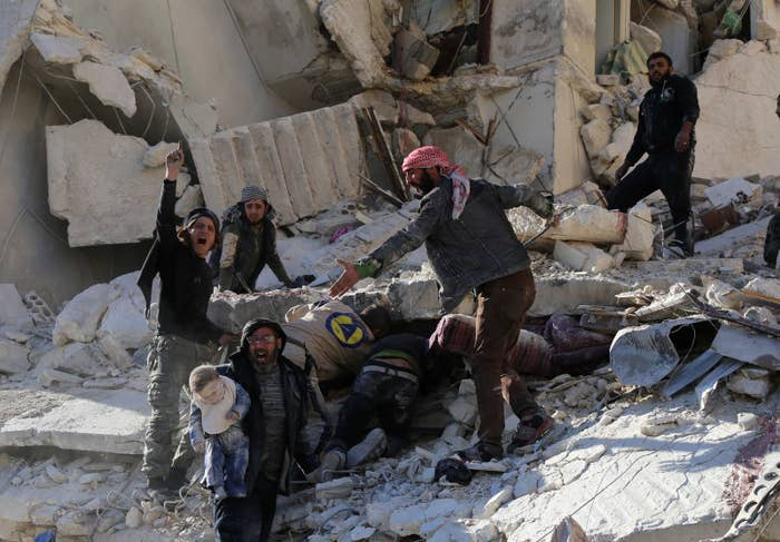 Civilians and rescue workers remove a toddler and search for other victims amid the rubble of a building following a reported airstrike by Syrian government forces on the Sukkari neighborhood. Dec. 7, 2015.