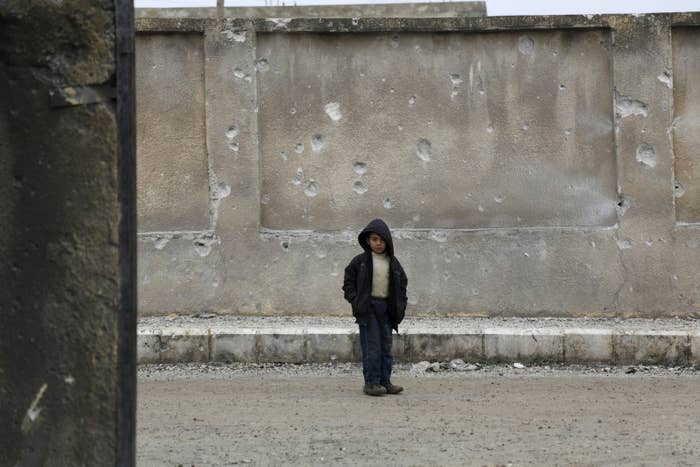 A boy stands near a wall of his school riddled with holes from an airstrike carried out by the Russian planes in the town of Injara in the Aleppo countryside. Jan. 12, 2016.