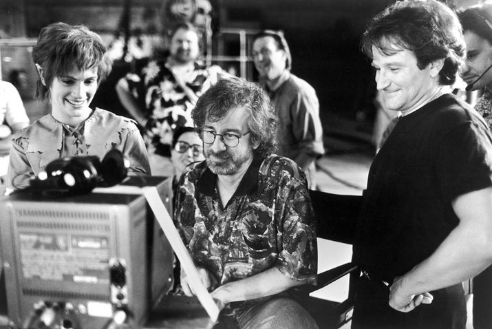 Julia Roberts and Robin Williams watch daily production footage with director Steven Spielberg on the set of Hook.