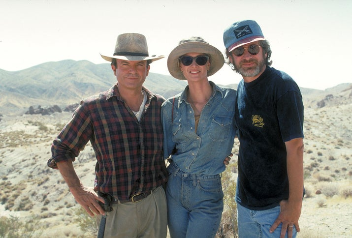 From left: actors Sam Neill and Laura Dern pose with director Steven Spielberg on the set of Jurassic Park.