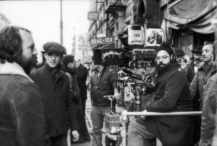 Director Francis Ford Coppola sits with a film camera on the set of The Godfather Part II. Robert De Niro is standing at left.