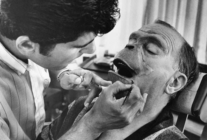 Foam-rubber makeup being applied to actor Maurice Evans.