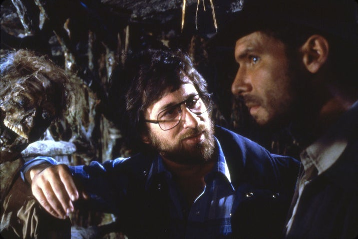 Director Steven Spielberg and actor Harrison Ford chat on the set of Raiders of the Lost Ark.