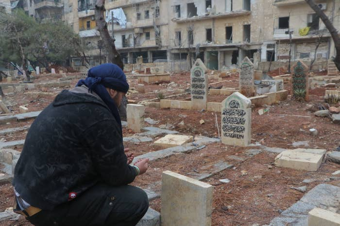 A man prays over the graves of family members in al-Mashhad.