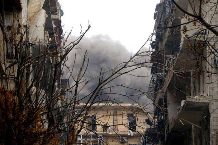 Smoke rises among damaged buildings in the al-Mashhad neighborhood in Aleppo after attacks of Assad forces and allied militias.
