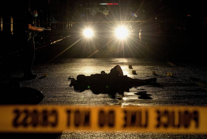 Police officers investigate a crime scene where two alleged drug dealers were gunned down by unidentified men in Manila.