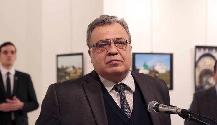 Ambassador Andrey Karlov speaking at the Ankara gallery on Monday. The suited man on the left was later filmed firing shots.