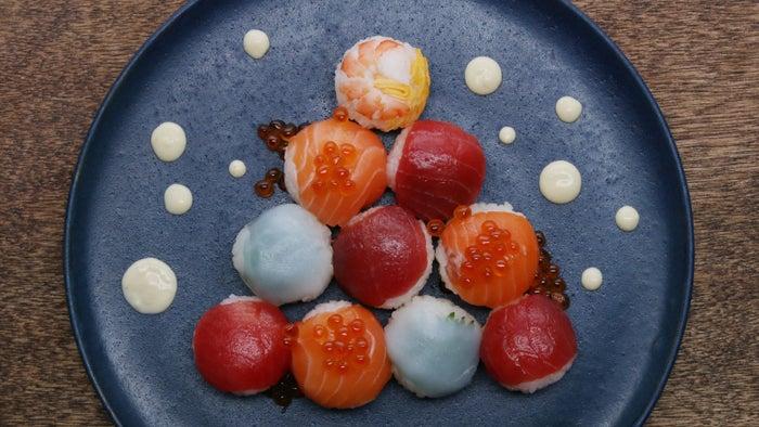 20個分材料ごはん(固めに炊く) 2合A.砂糖大さじ3A.酢 大さじ3A.塩 小さじ1まぐろ適量サーモン 適量いか 適量大葉 適量ボイルえび 適量いくら 適量<錦糸卵>卵 1個片栗粉大さじ1水 大さじ2<わさびマヨ>マヨネーズ 大さじ2わさび大さじ11.まぐろ、サーモン、いかはさくを大きめになるように切る。または切り身をラップで包んで上からたたいてのばす。ボイルえびは横半分に切る。大葉は茎を除いて半分に切る。2.錦糸卵を作る。ボウルに材料を入れてよく混ぜ合わせ、裏ごしする。フライパンに流し入れて薄焼き卵を作り、冷ましたらロール状に巻いて端から千切りにする。3.固めに炊いたごはんに(A)を加え、しゃもじで切るように混ぜる。4.ラップにまぐろをのせ、(3)を30gのせて包み、丸くなるように形を整える。5.ラップにサーモンをのせ、(3)を30gのせて包み、丸くなるように形を整える。6.ラップにいかと大葉(裏面が表になるように)をのせ、(3)を30gのせて包み、丸くなるように形を整える。7.ラップにボイルえび(裏面が表になるように)と錦糸卵をのせ、(3)を30gのせて包み、丸くなるように形を整える。8.わさびマヨを作る。材料をよく混ぜ合わせ、小さめのビニール袋などに入れて、先端を切ってコルネ状にする。9.皿に手まり寿司をバランスよく並べ、雪に見立てたわさびマヨを絞ったら、完成!